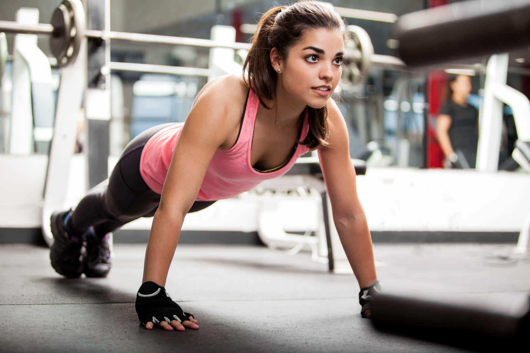 woman holds plank in gym