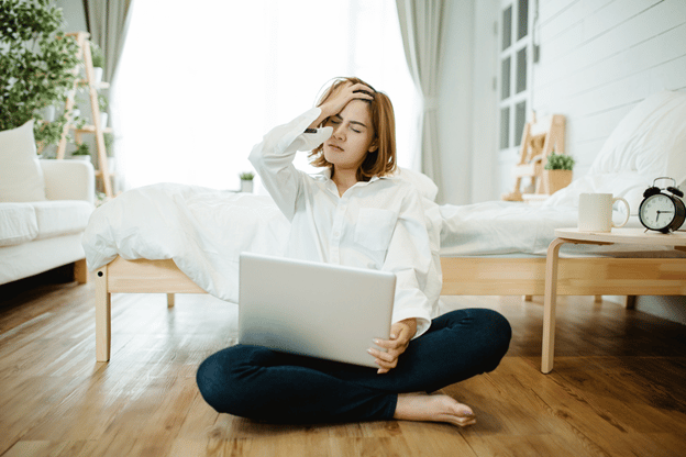 woman holding head with laptop in lap