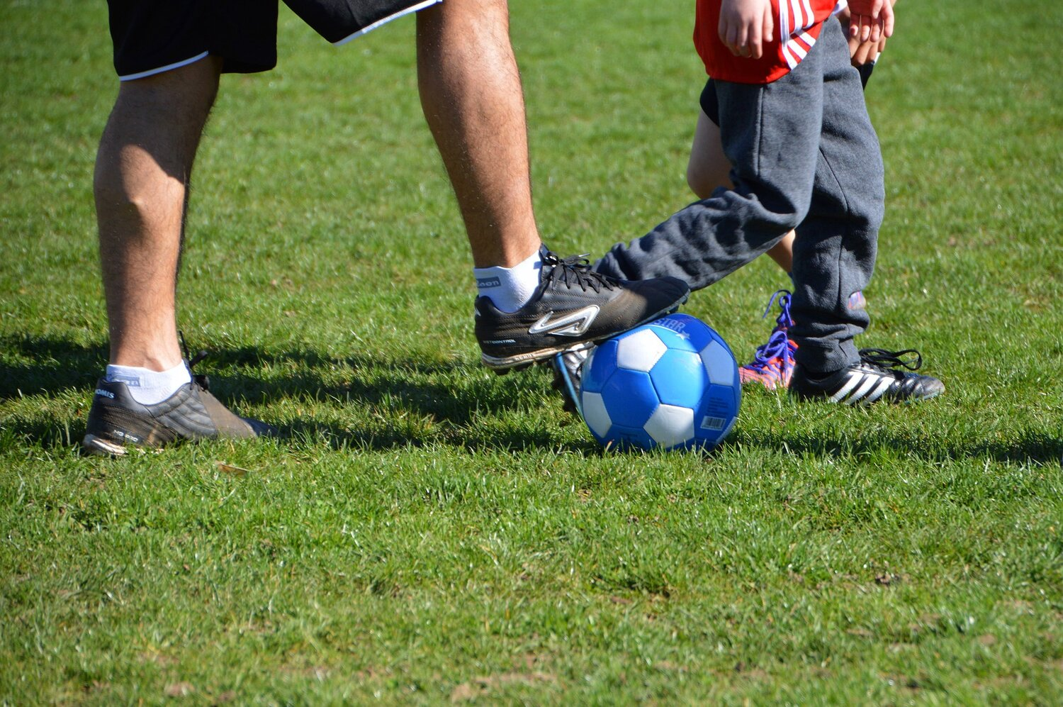man and child playing football