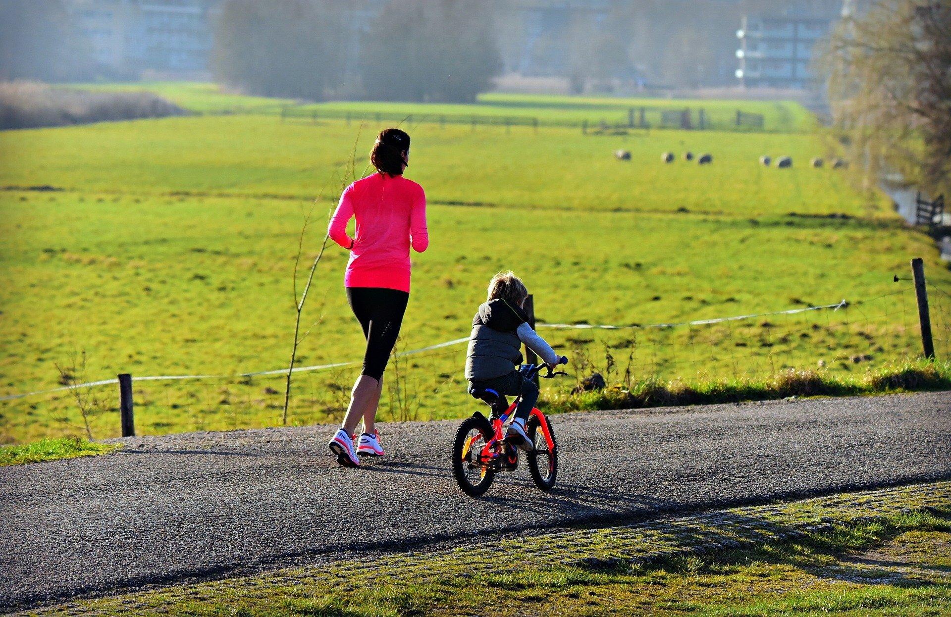 mum running with child on bike