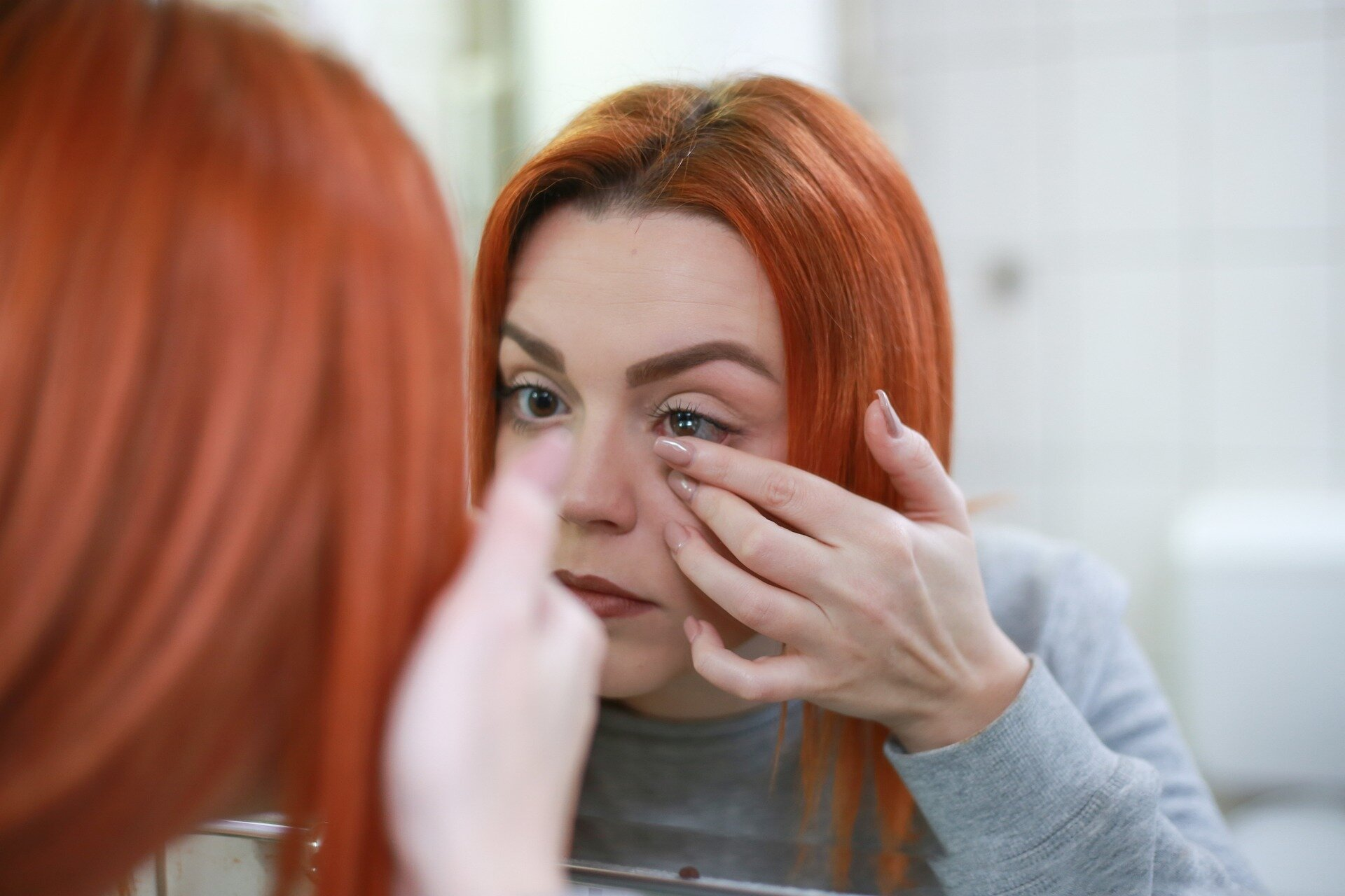 woman putting contact lenses in eye
