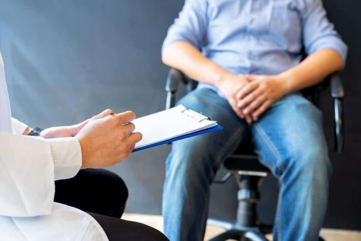 man speaks to dr with clipboard