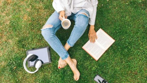 woman sits on grass with coffee and book