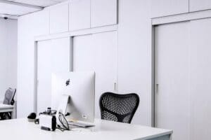 black mesh office rolling chair beside white wooden desk 217294
