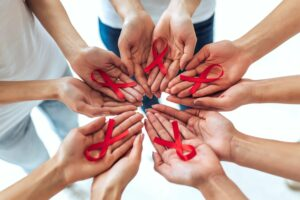 hands holding red ribbons for aids day