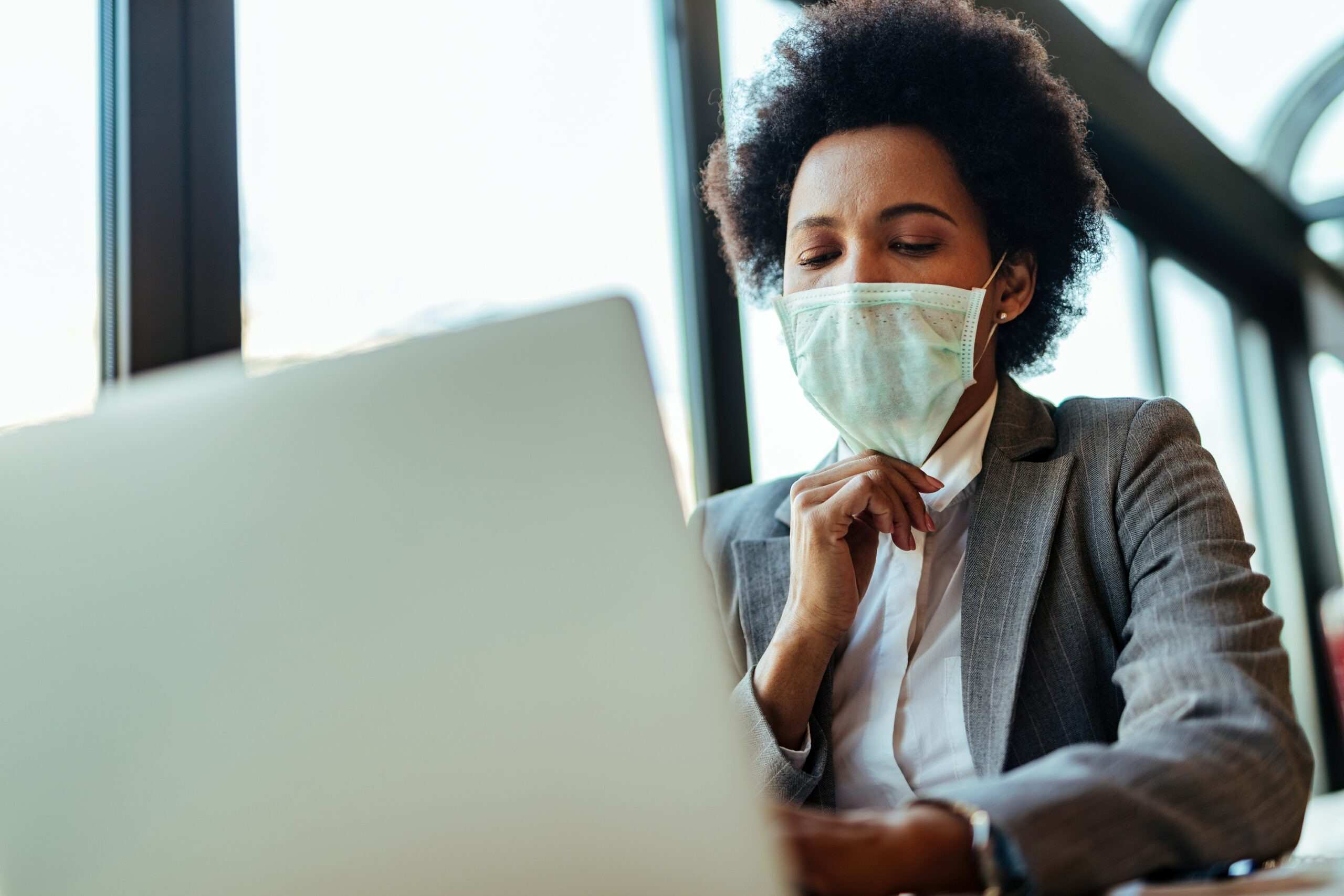 woman at desk with facemask scaled