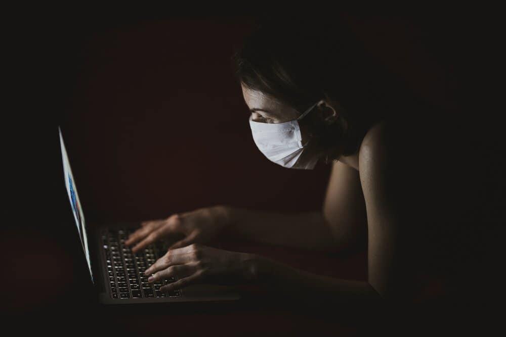 woman wearing face mask using macbook pro 4031902