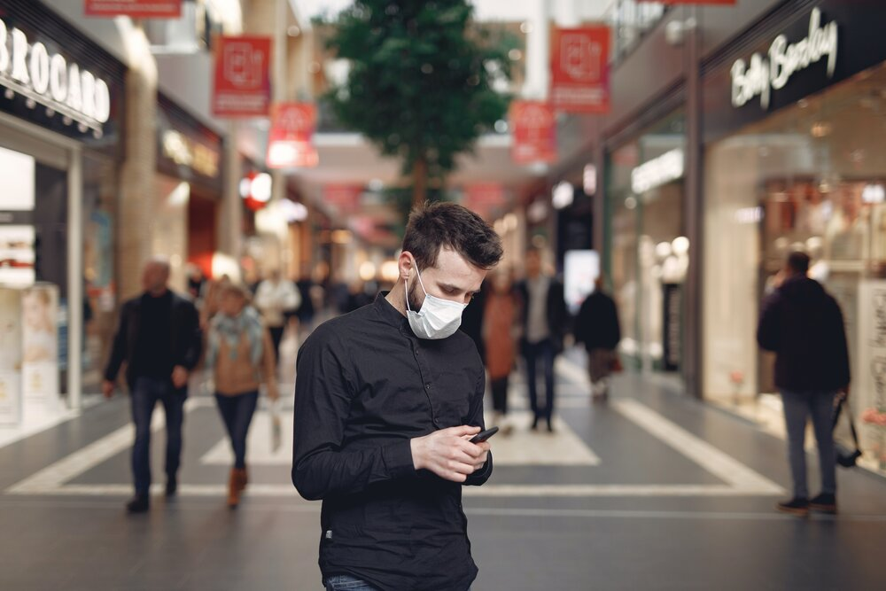 young man in disposable mask using smartphone in middle of 3983435