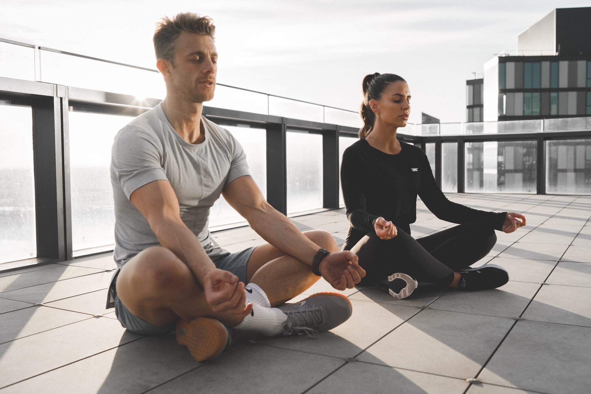 couple meditate on roof top