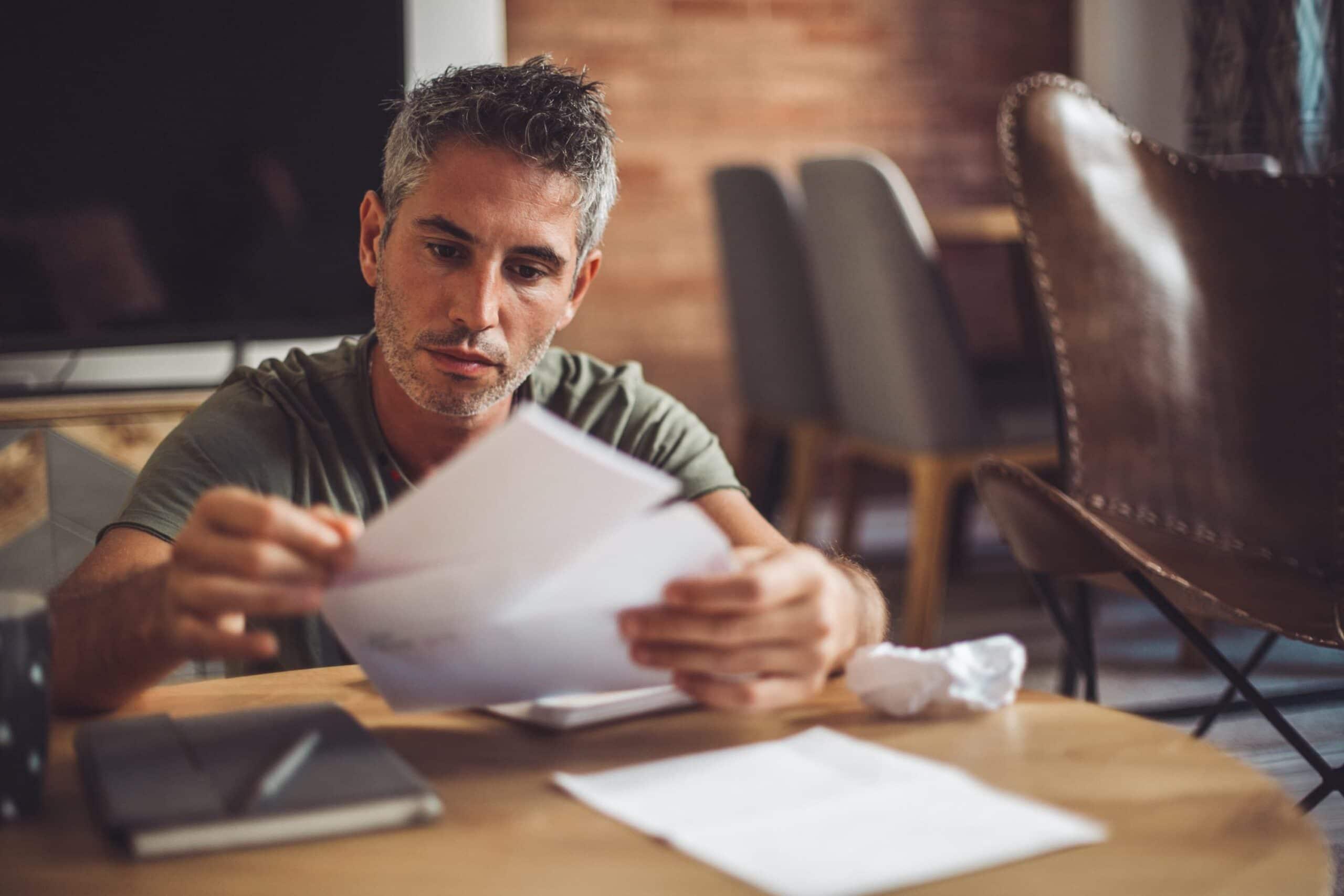 man looking through bills scaled