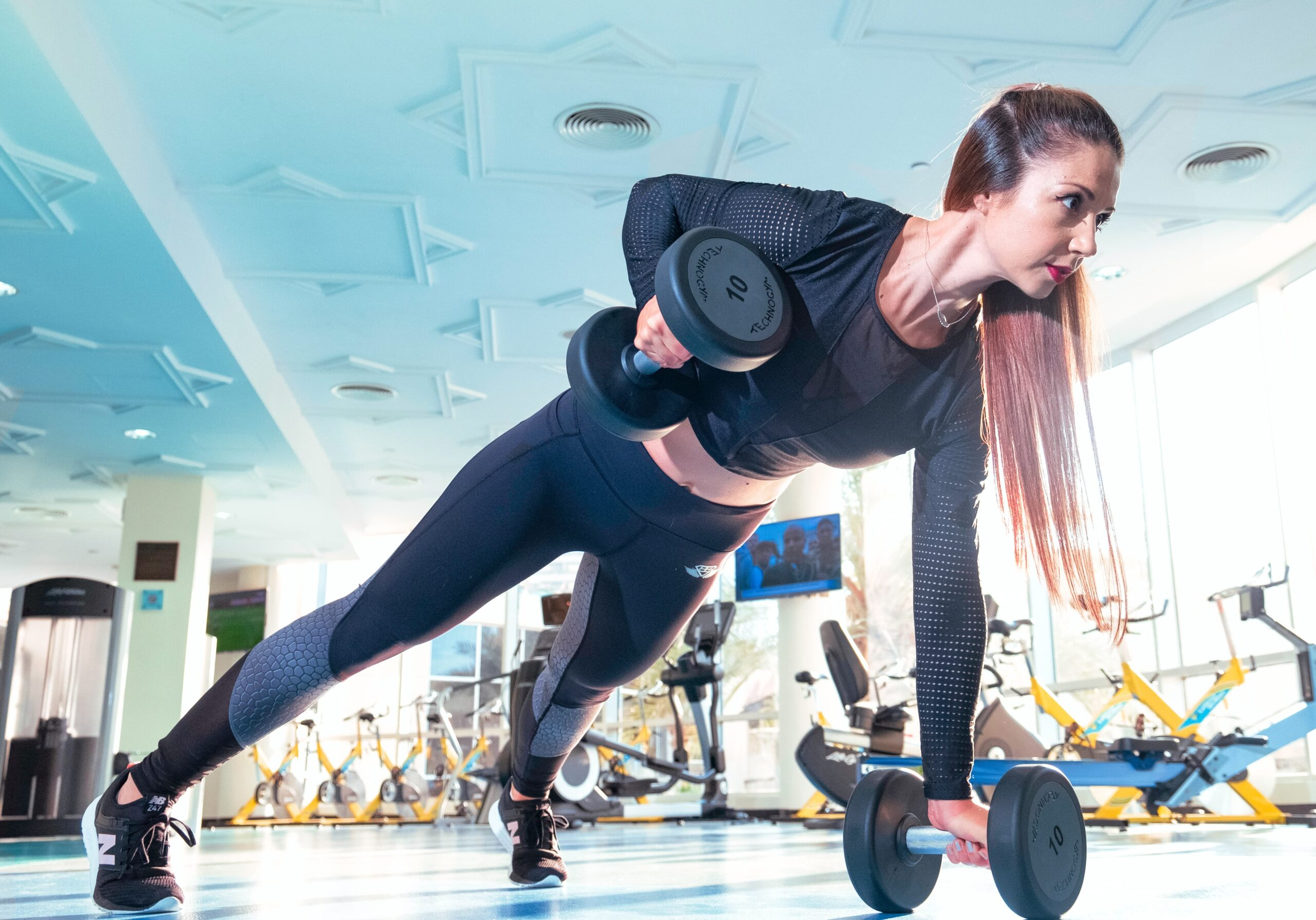 woman lifts dumbbell in gym scaled
