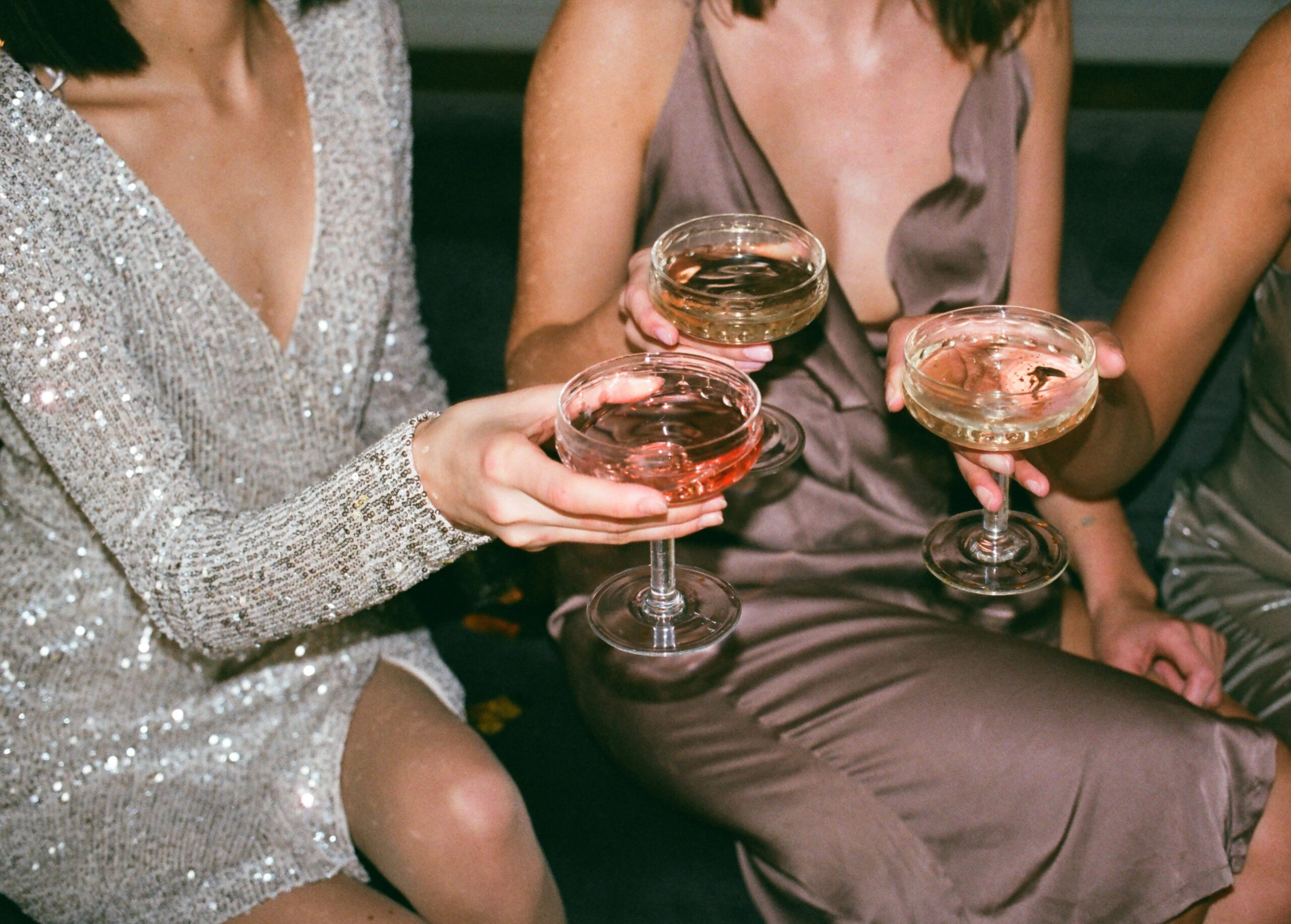 women hold out drinks together scaled