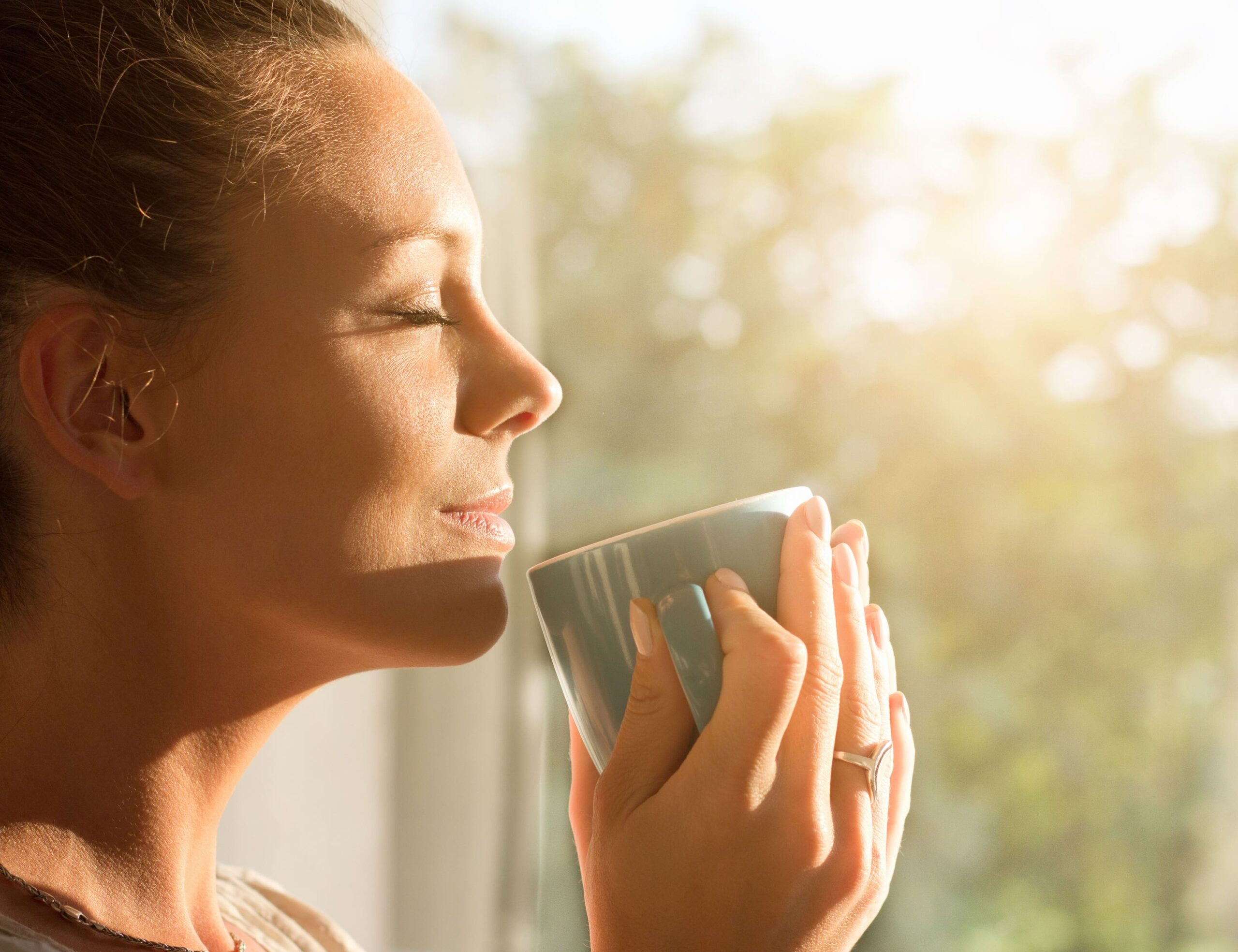 woman holding cup smiles in the sunshine scaled