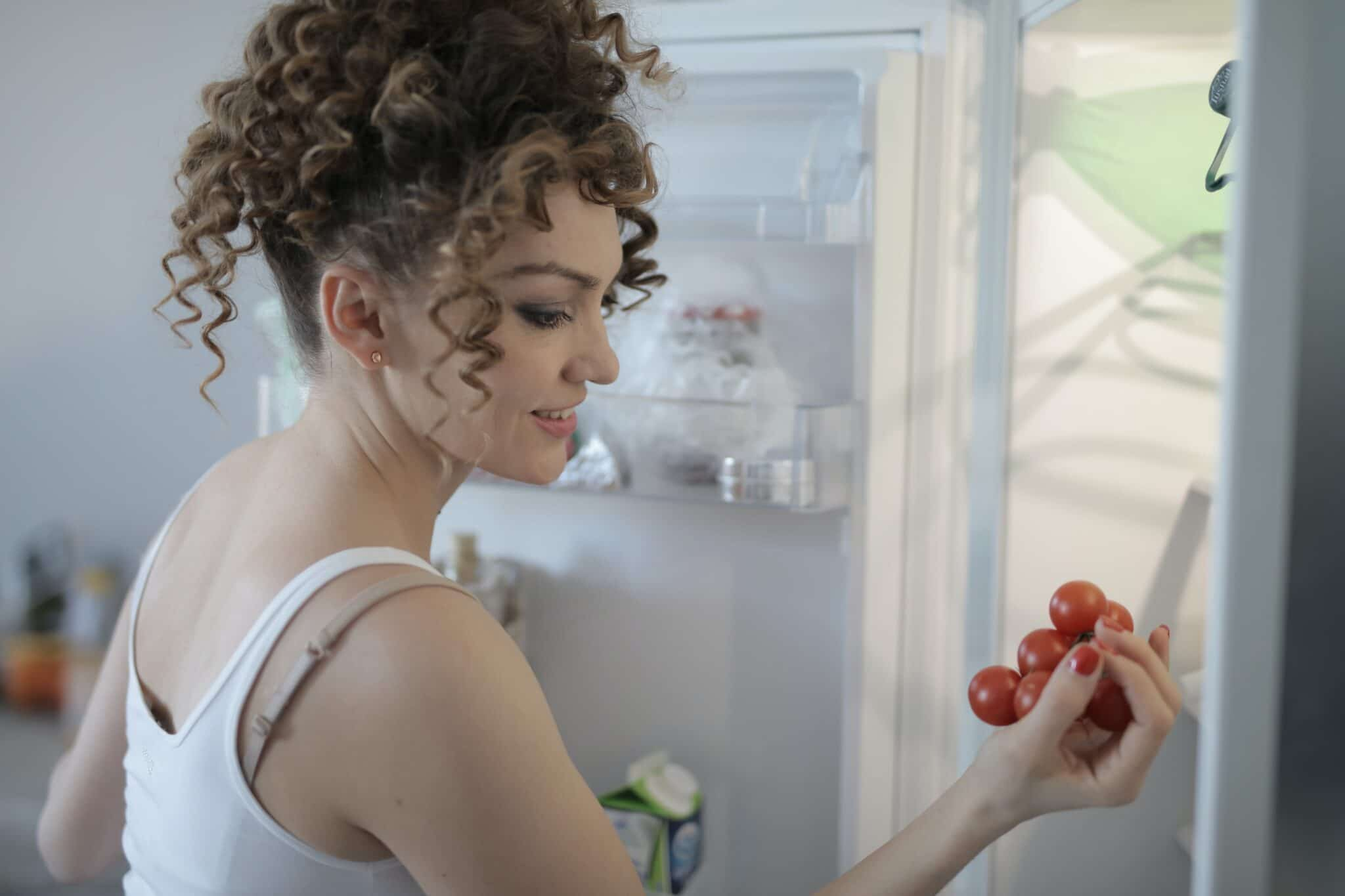 woman looking at tomatoes in fridge
