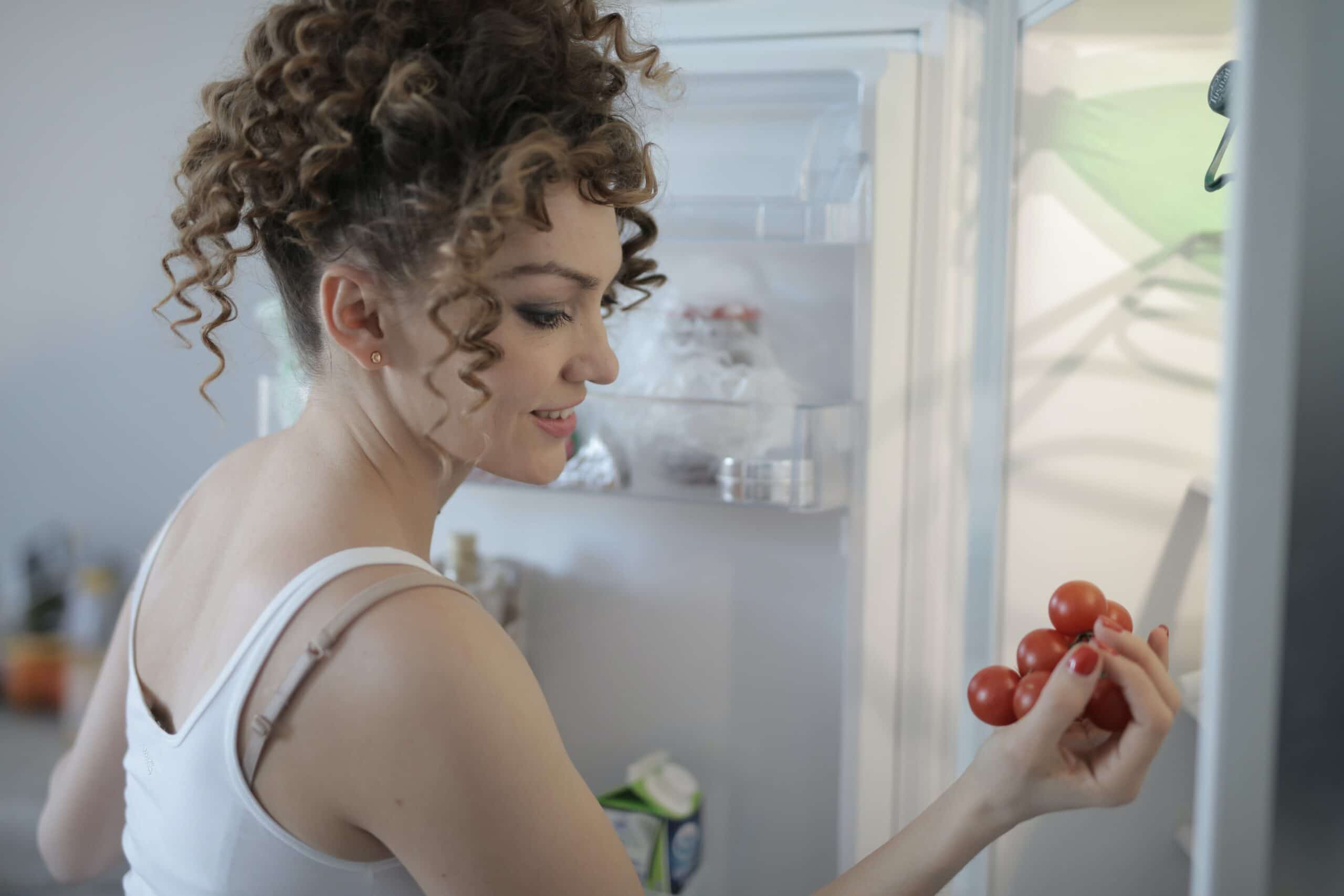 woman looking at tomatoes in fridge scaled