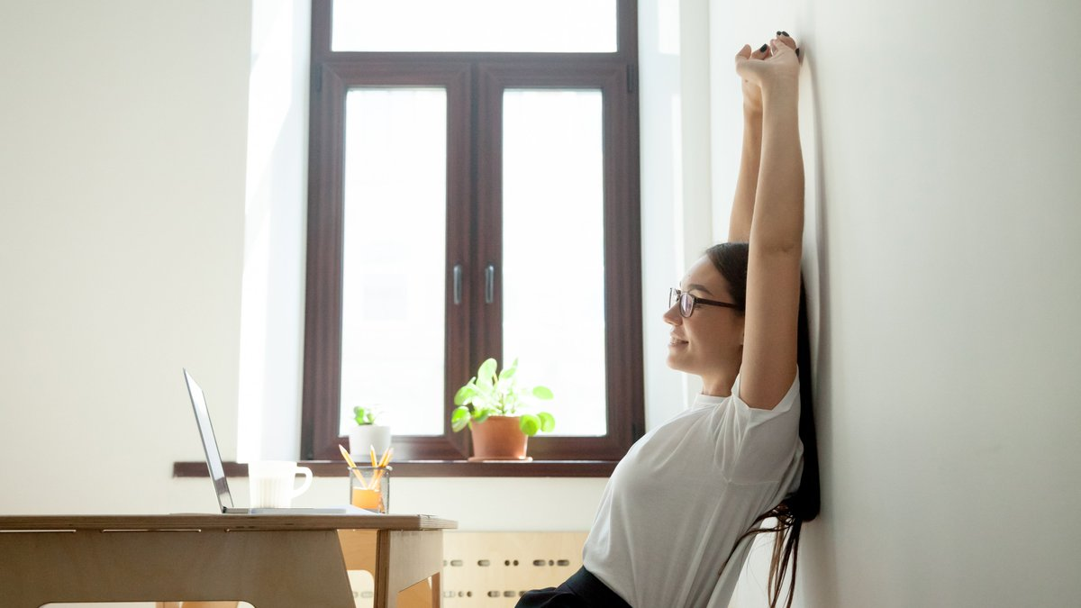 woman stretches back against a wall