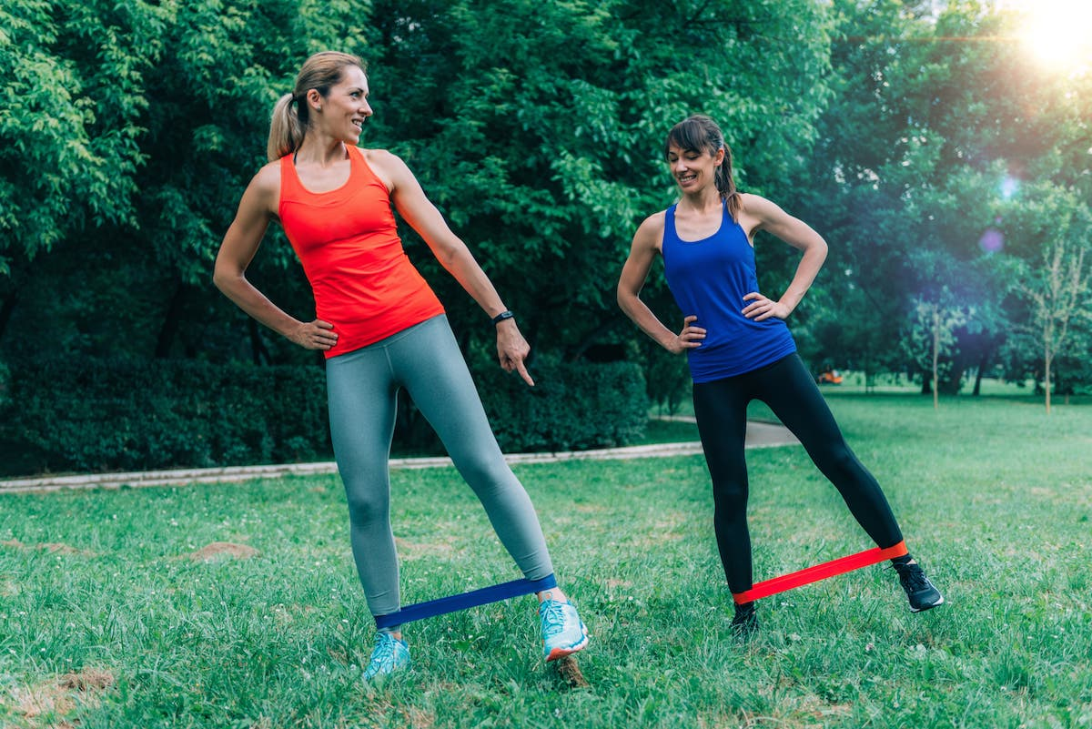 women with resistance bands train outdoors
