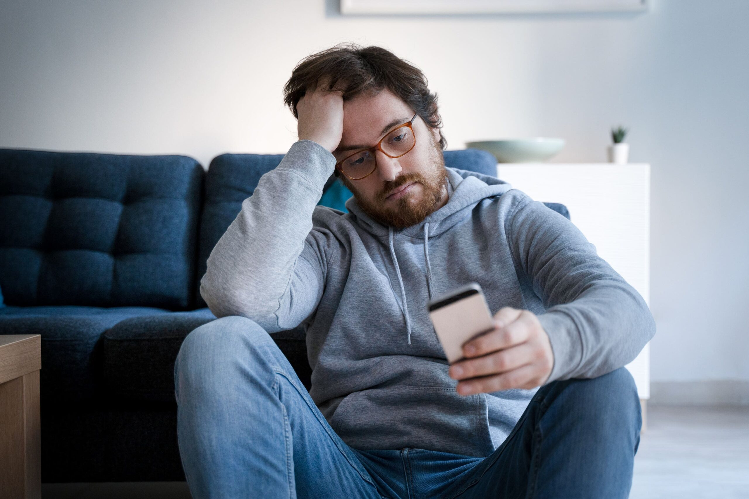 man looks stressed looking at phone scaled