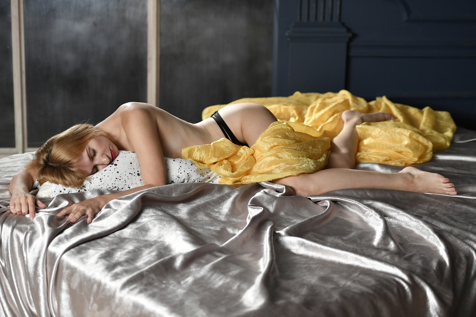 woman lays half naked on bed