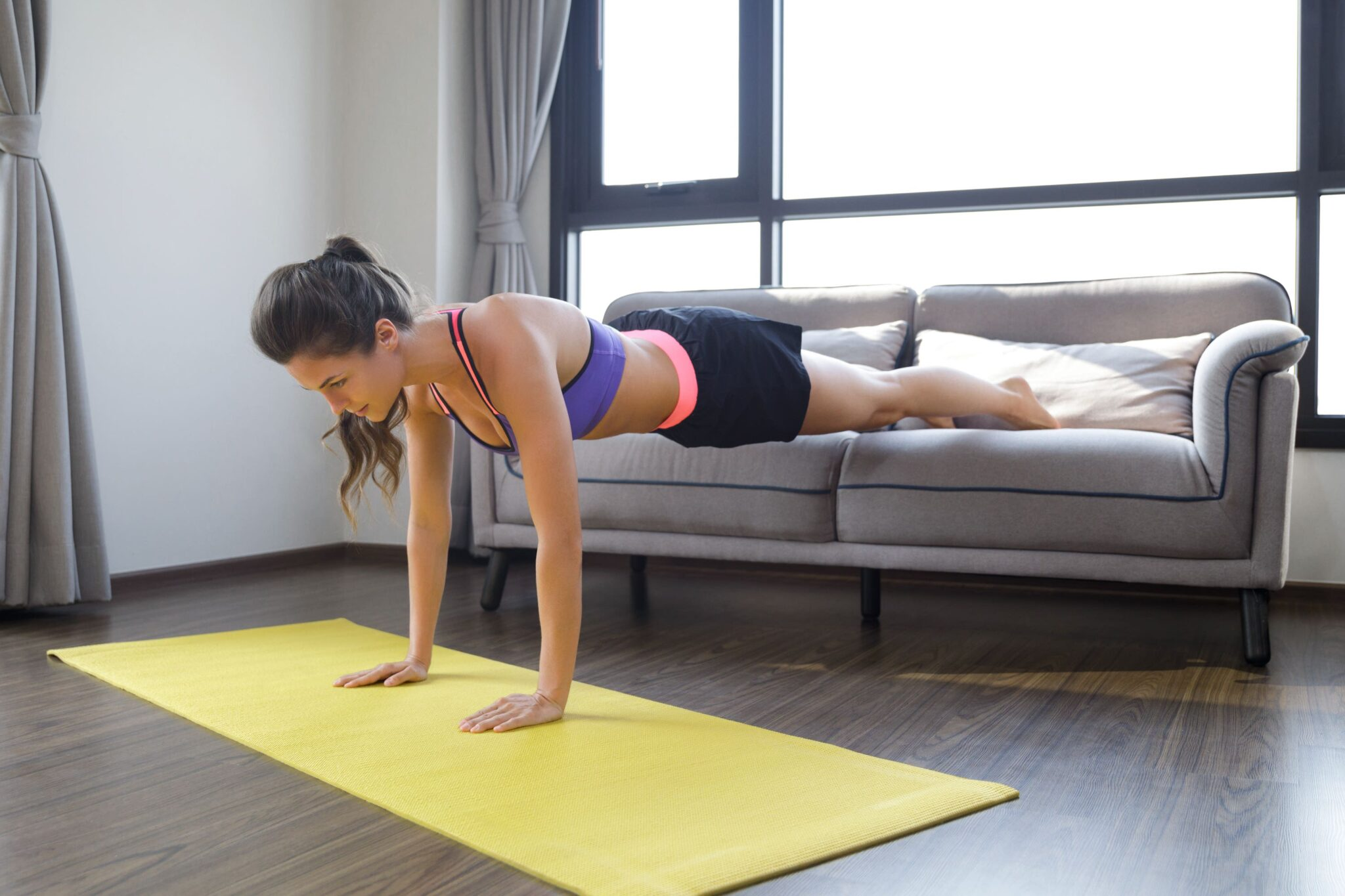 woman planks from sofa