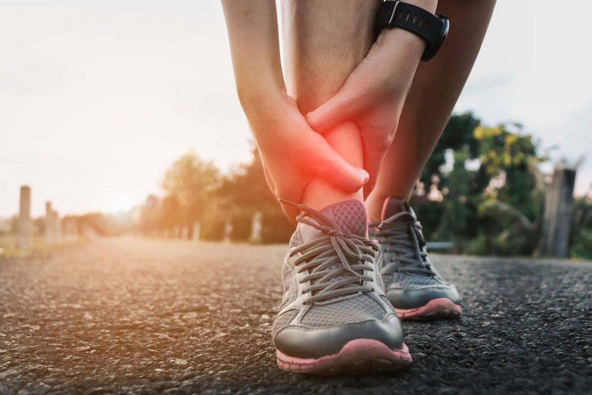 athlete holds ankle in pain