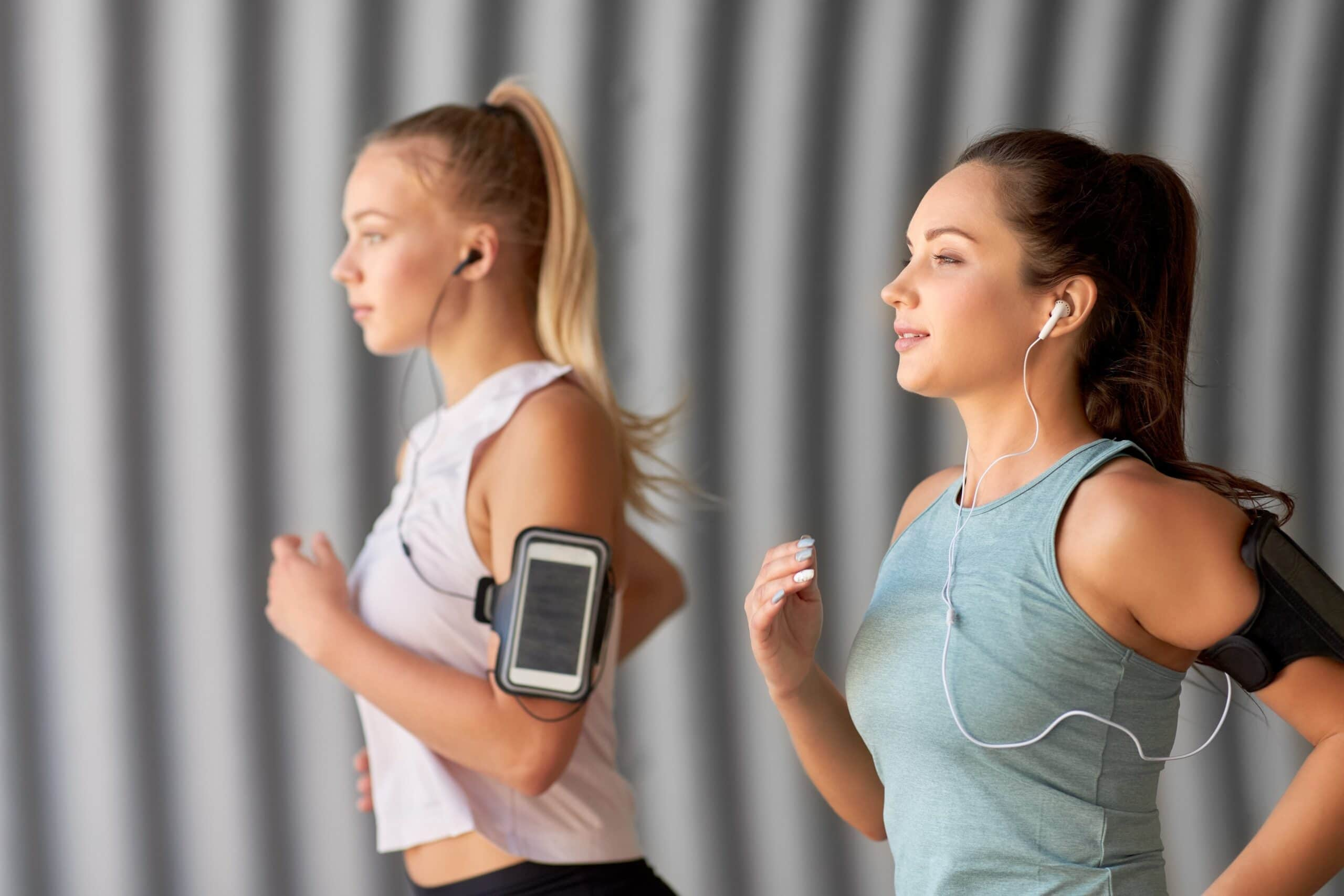 female runners with headphones in scaled