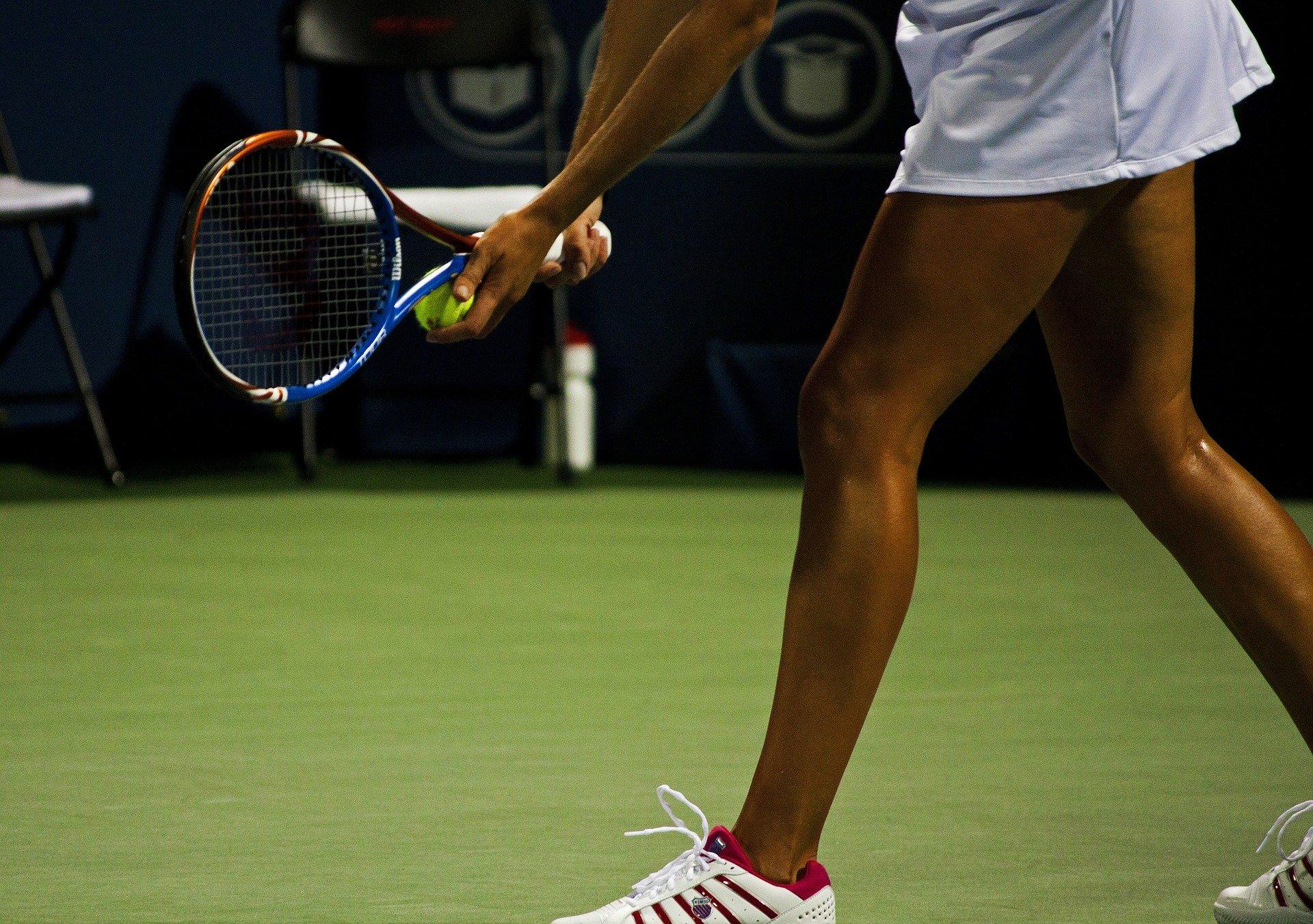 tennis player lines up serve
