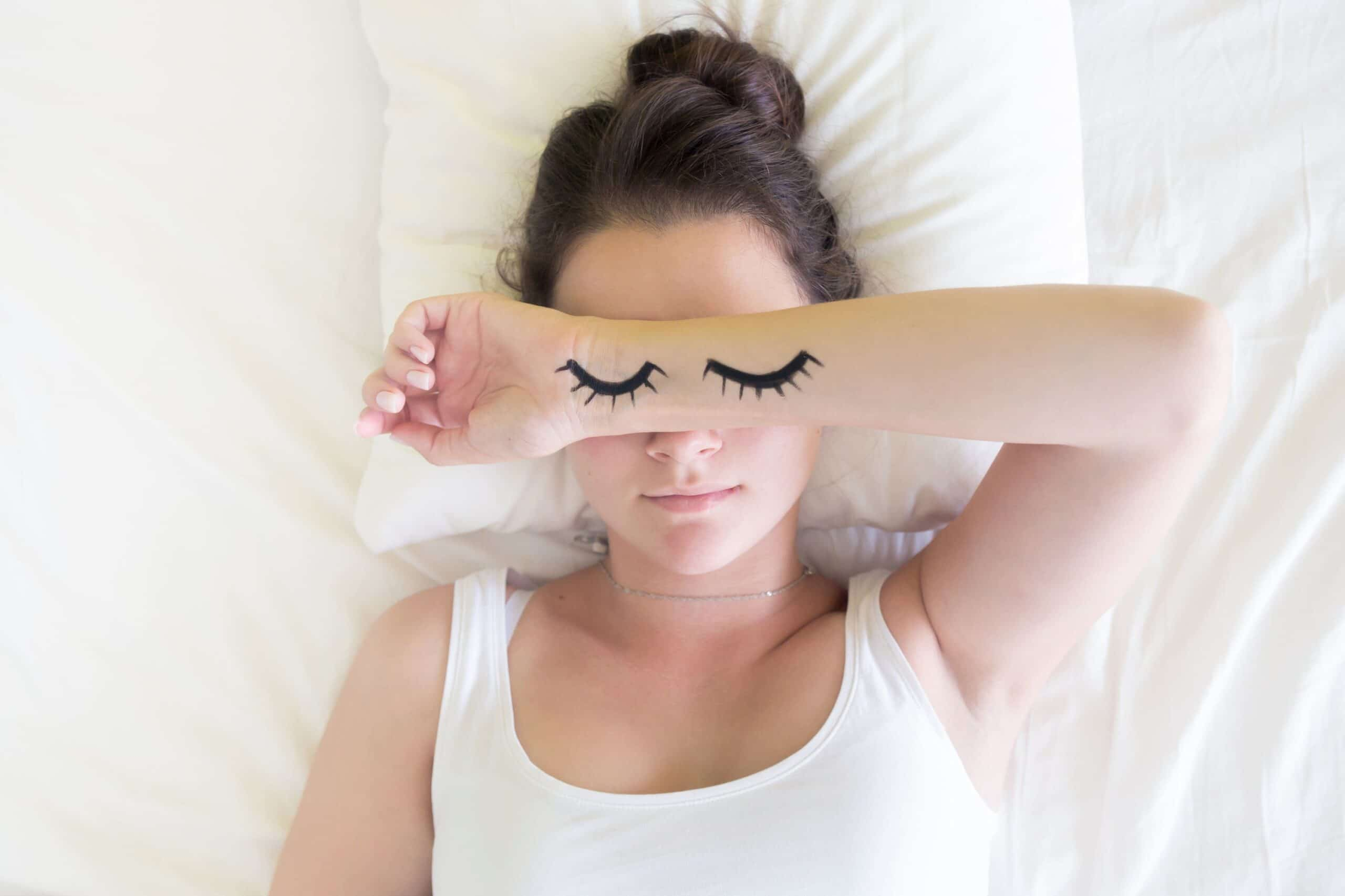 woman sleeps with eyes drawn on arm scaled
