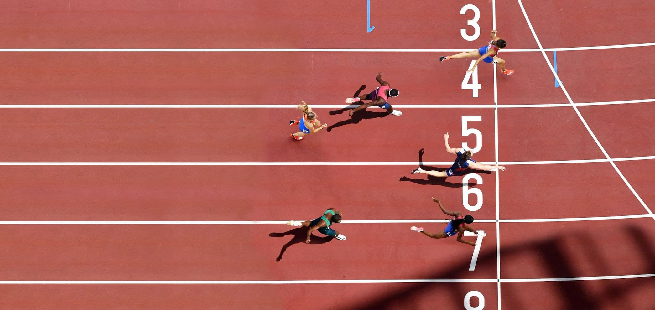 olympic runners cross the finish line