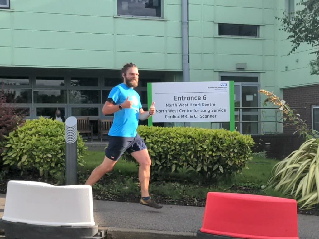 Alan Day running past some of the signage at Wythenshawe Hospital