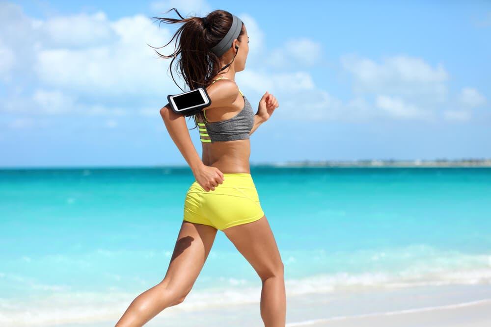 female runner runs along the sea