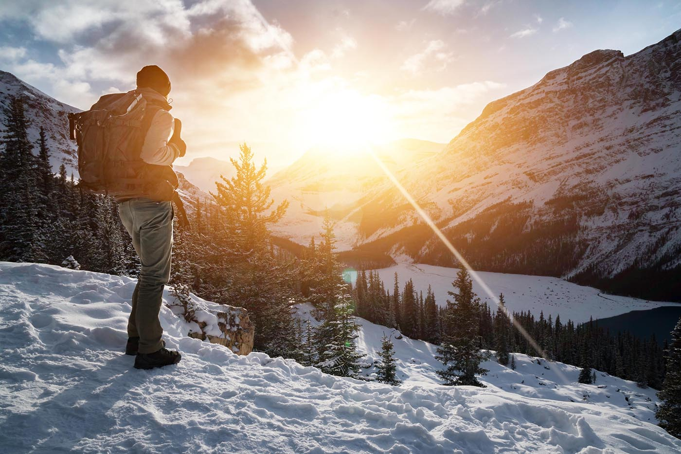 mountain hiker looks out over snowy mountains