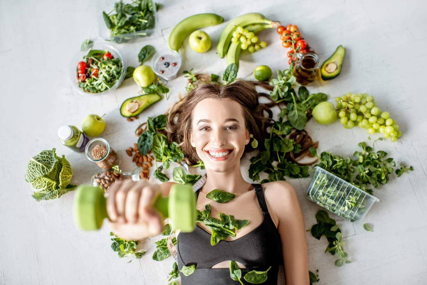 sports woman surrounded by various healthy food lying on the floor