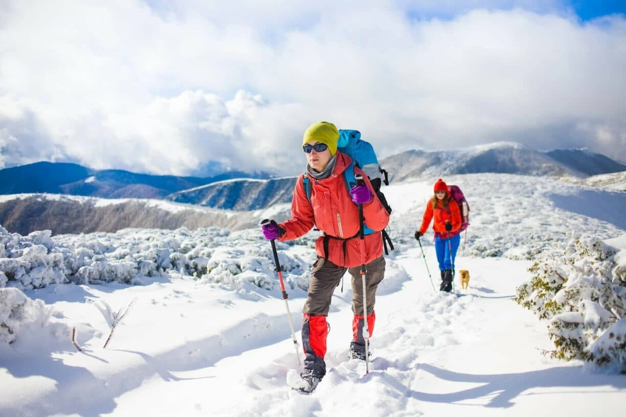 two female hikers climb mountains covered in snow