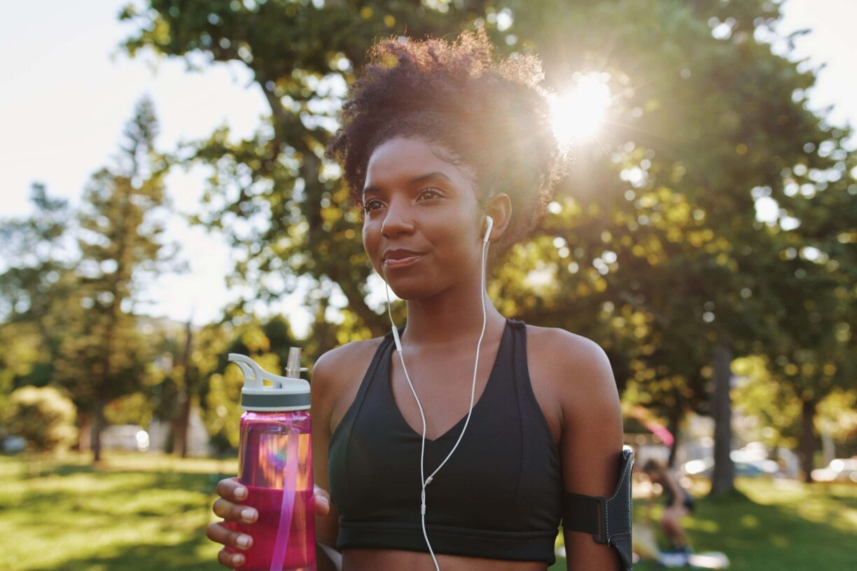 woman holds water bottle in park