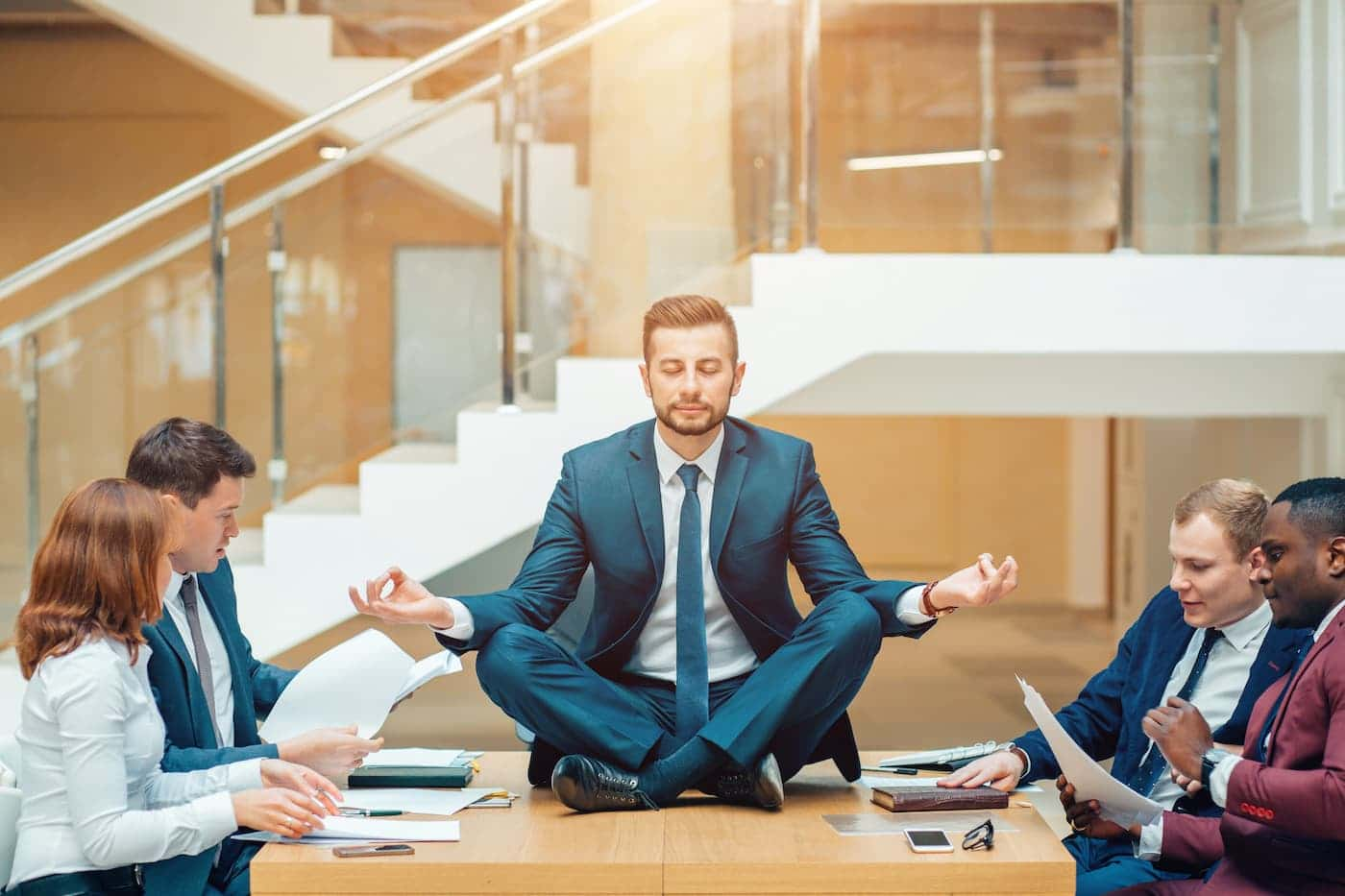 Businessman wearing a suit doing Yoga on the table