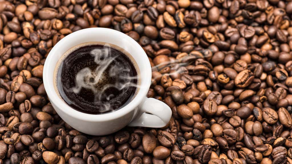 hot coffee in cup surrounded by coffee beans