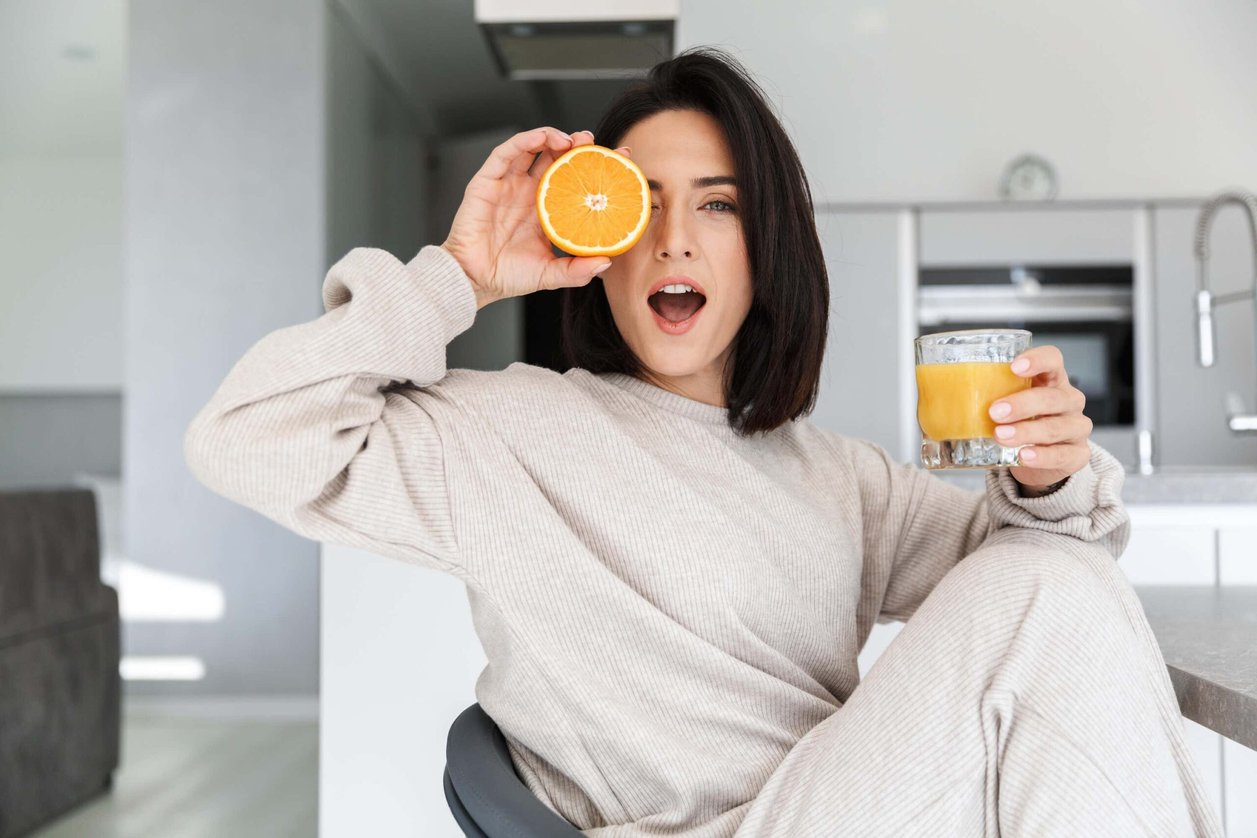 woman holds half an orange to her eye scaled