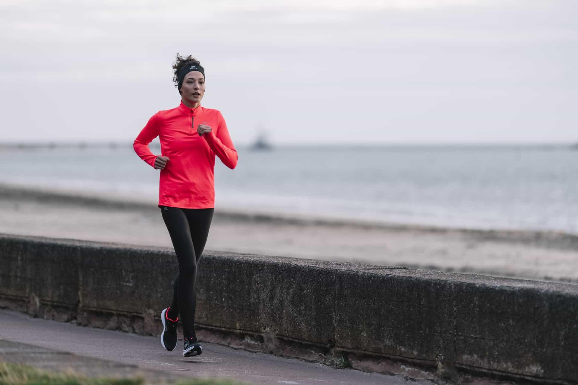 woman runs by sea wall