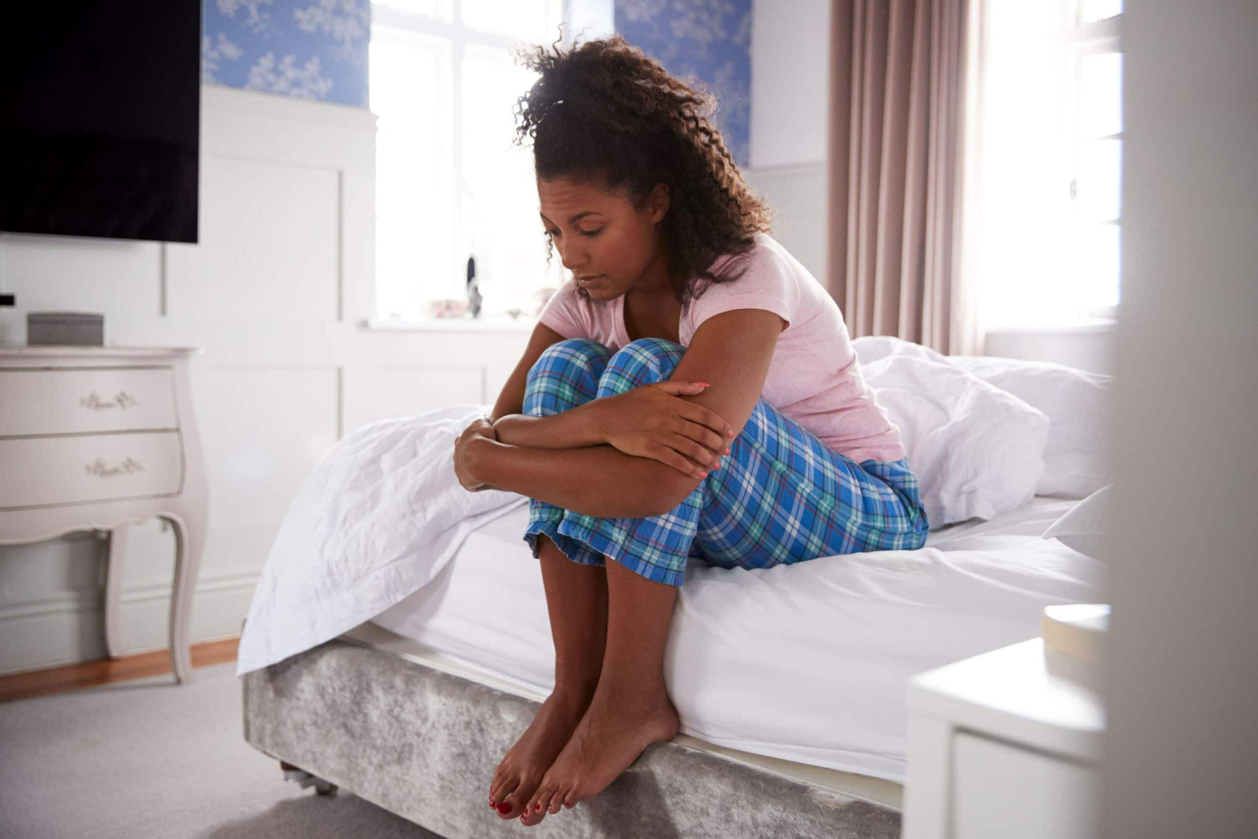 woman sits on end of bed looking anxious scaled
